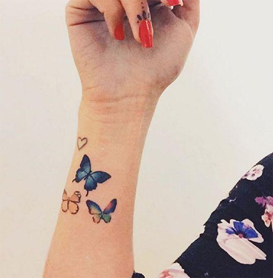 mariposas volando tatuadas en la mano