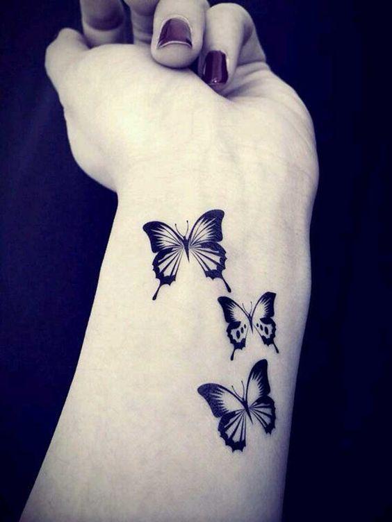 tres mariposas tatuadas en el antebrazo de una mujer