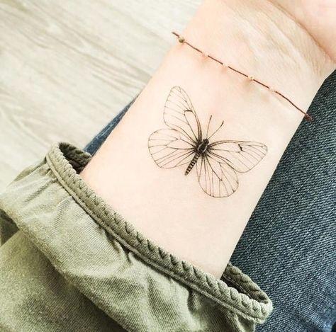mariposa tribal tatuada en la muñeca