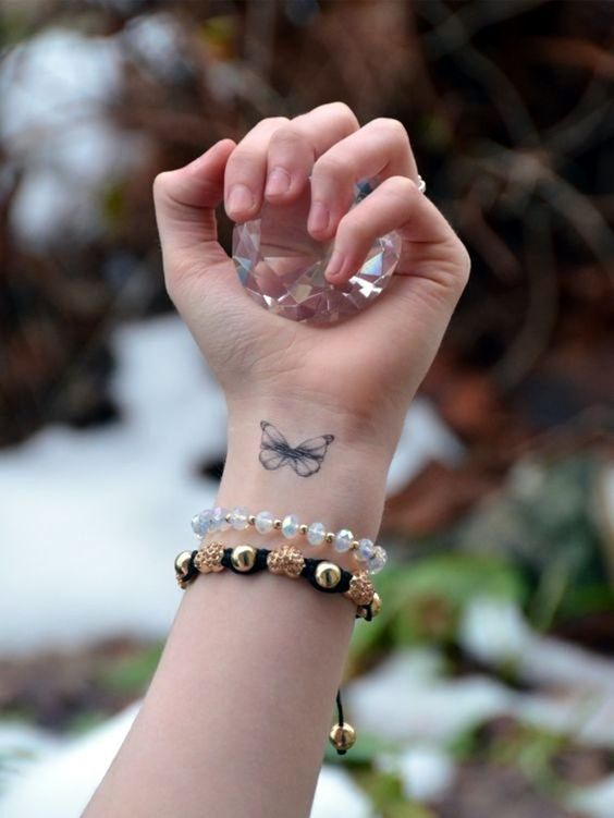 mariposa simple tatuada en la mano