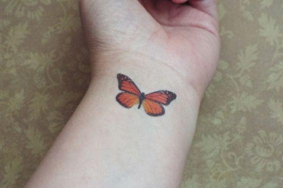 mariposa tatuada en el brazo