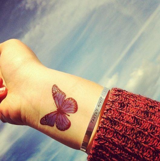 un tatuaje de color rojo con el diseño de una mariposa en el brazo de una mujer