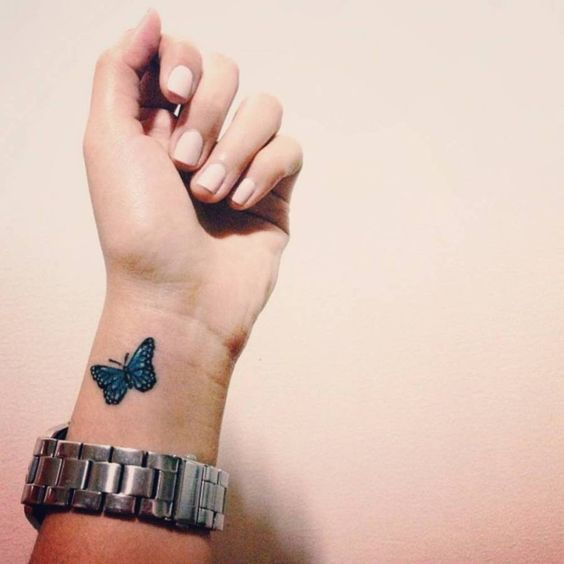 Una mariposa azul tatuada en la muñeca