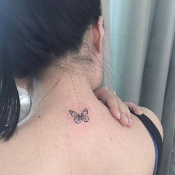 Pequeña mariposa tatuada en la nuca