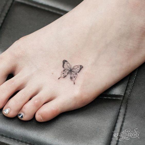 Un diseño tribal de mariposa tatuada en el pie