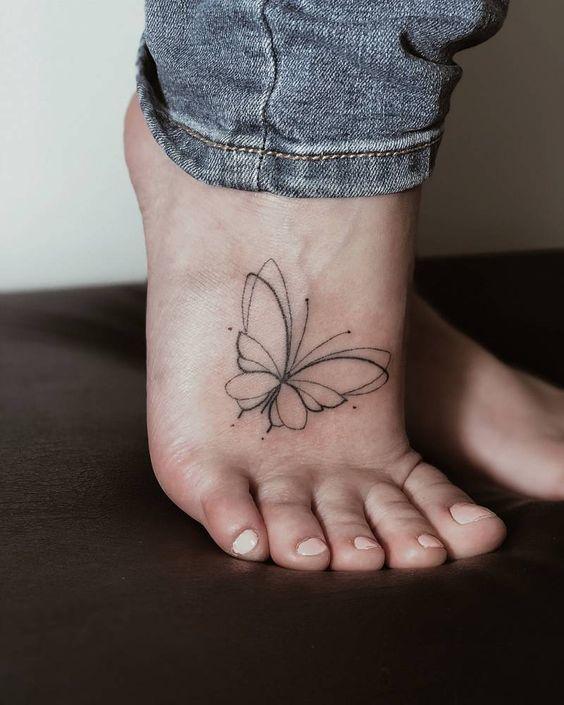 Diseño de mariposa tribal en el pie de una chica