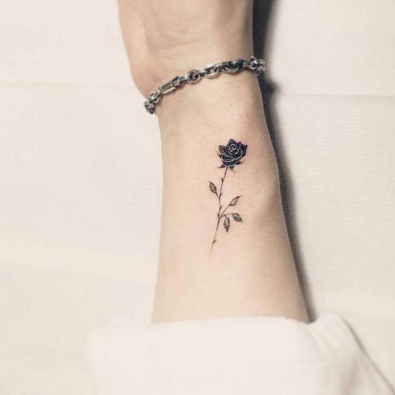 Mujer con el brazo tatuado con una rosa pequeña