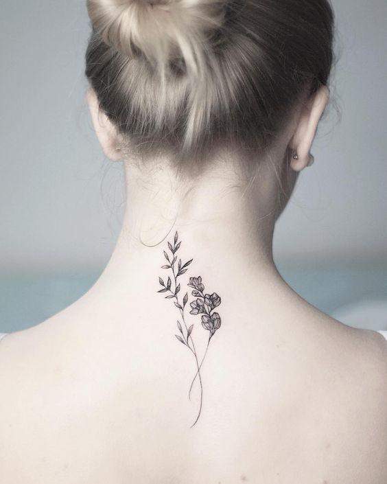 Una rosa junto a su tallo tatuada en el medio de la espalda