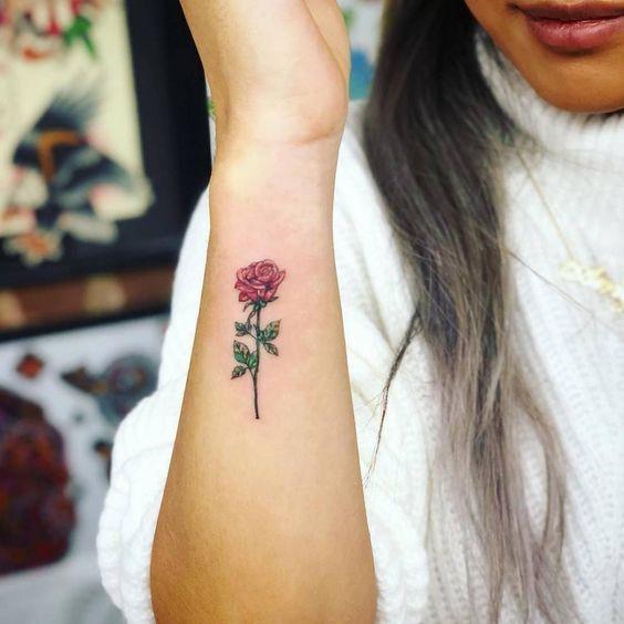 Tatuaje de rosa de color rosa en el antebrazo