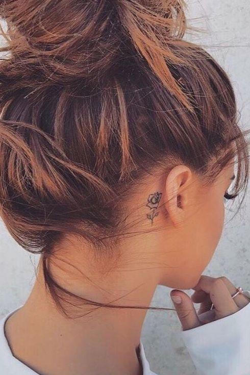 Chica con el cabello recogido mostrando el tatuaje de una rosa pequeña detrás de su oreja