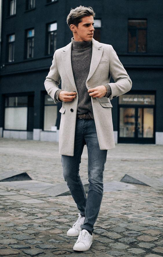 Hombre con chaqueta clara y zapatillas blancas