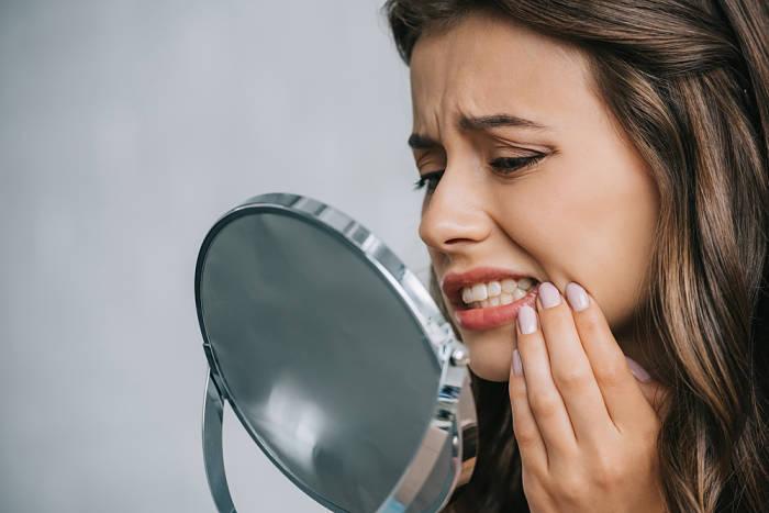 Mujer joven con problemas en las encías por estrés