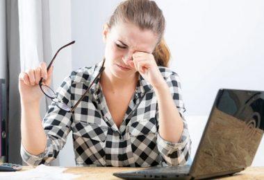 Frotarse los ojos puede deformar la córnea. Mujer frotando sus ojos.
