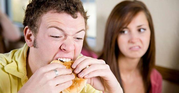Hombre comiendo hamburguesa, mujer mal humor