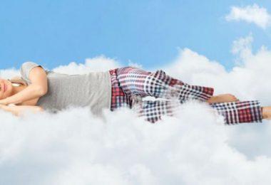 Mujer durmiendo sobre nube. Mujeres necesitan dormir más tiempo.