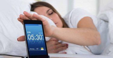 Mujer posponiendo alarma por no poder levantarse por las mañanas
