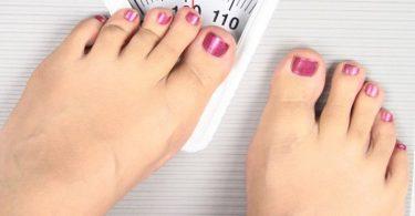 Mujer pesándose en la balanza