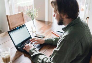 hombre escribiendo en computadora para trabajo en casa