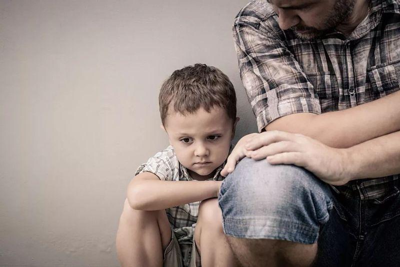 Padre junto a su hijo que está triste por el encierro y no ver a sus amigos