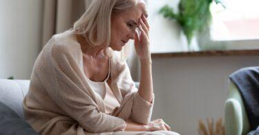 Mujer que padece síntomas de menopausia y requiere una dieta para aliviar los sofocos