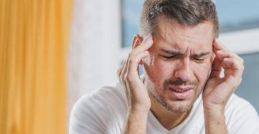 Hombre con dolor de cabeza por deficiencia de minerales