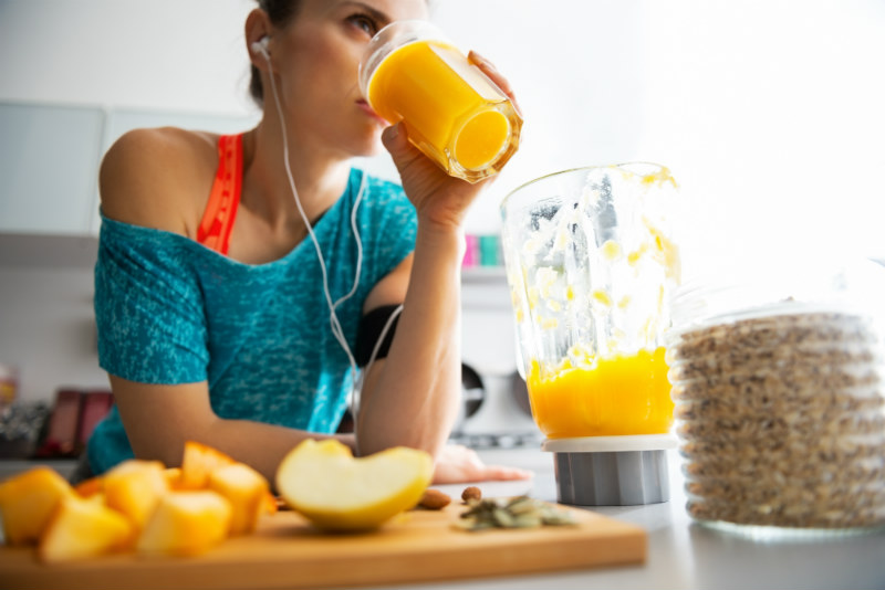 Mujer que hace deporte tomando jugo de naranja