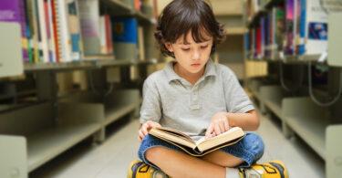 Nene leyendo en la biblioteca