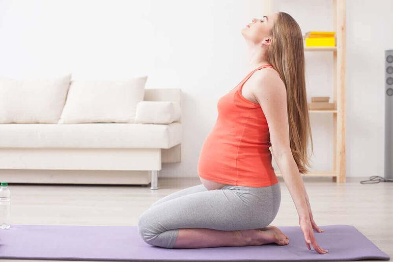 Mujer embarazada haciendo ejercicio de pilates