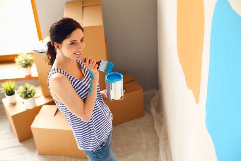 Mujer pintando su casa