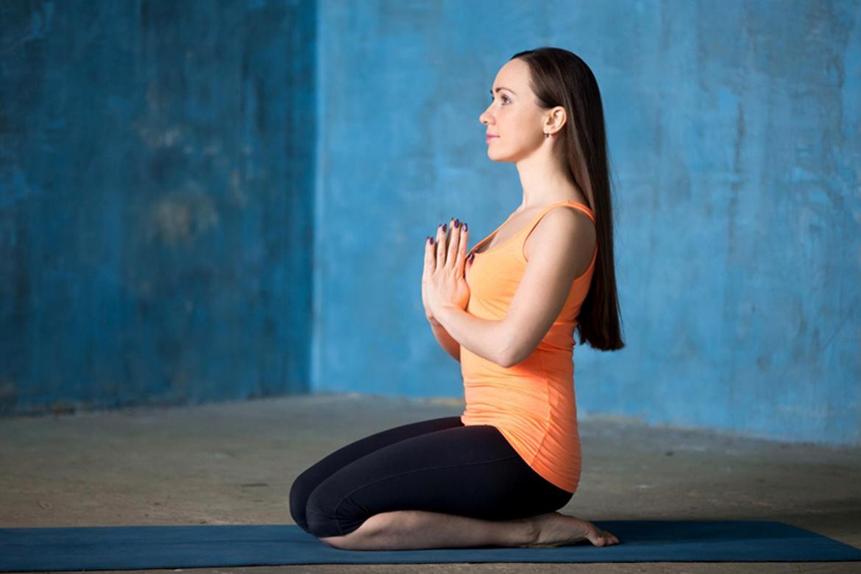Mujer sentada en la posición vajrasana
