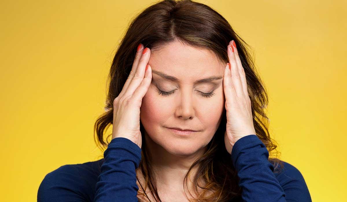 Mujer con dolores de cabeza por la menopausia