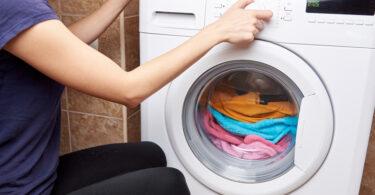 Mujer metiendo ropa para lavar en lavadora eléctrica