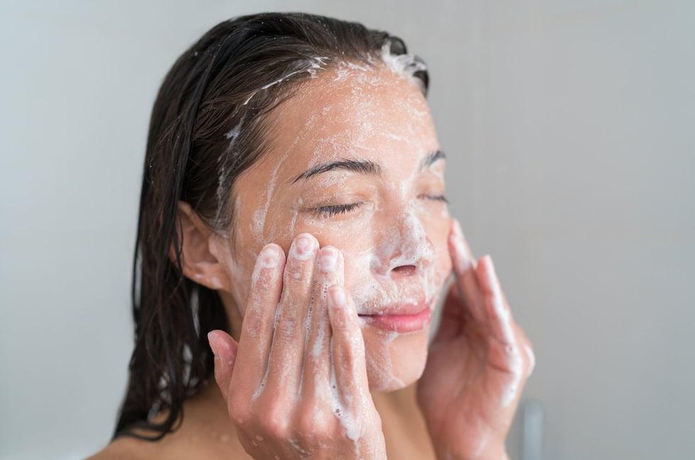 Mujer limpiando la piel de su cara