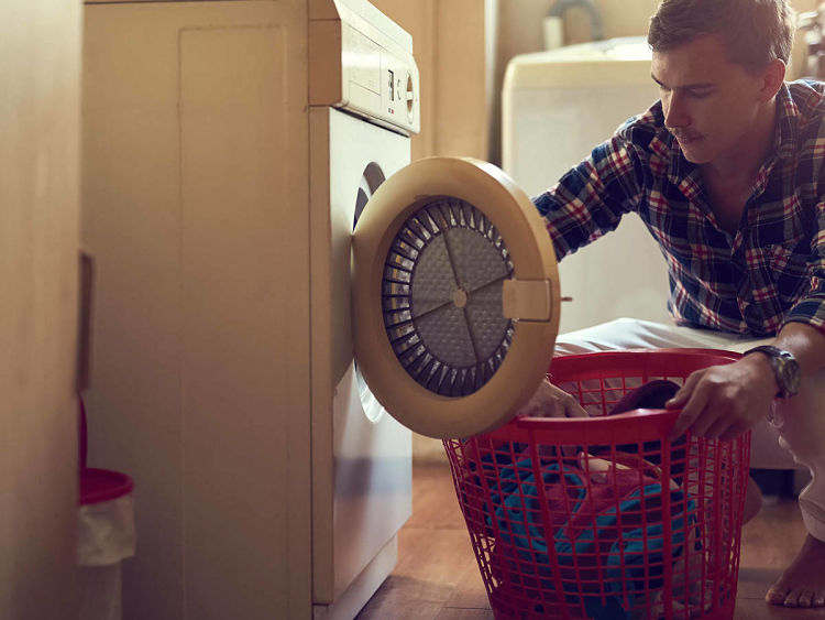 Persona que está poniendo ropa en la secadora