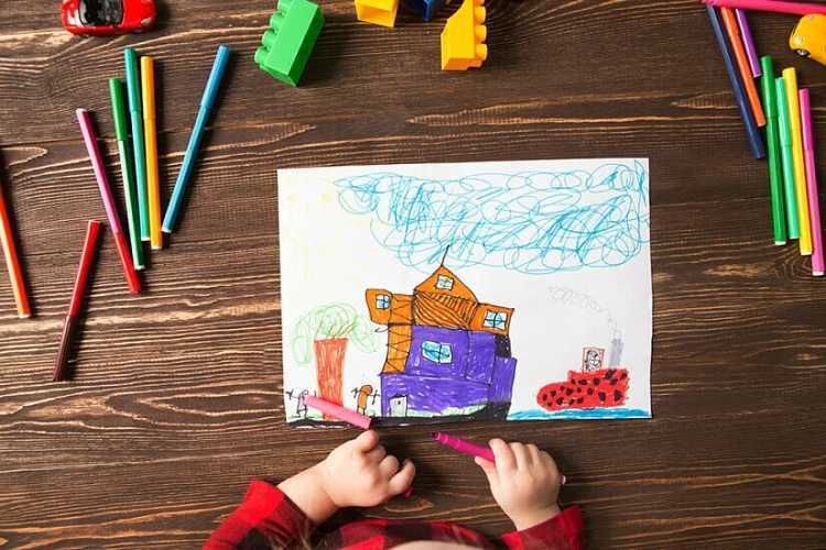 Niño haciendo un dibujo de una casa