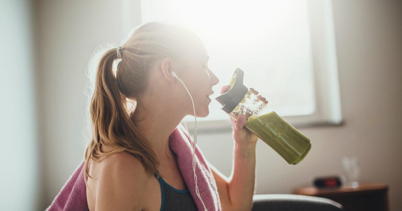 Mujer tomando un jugo verde para desintoxicar el cuerpo