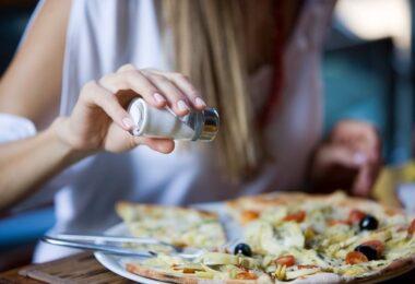 Mujer agregando sal a la comida