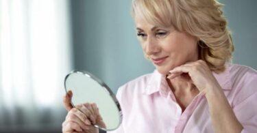 Una mujer mayor viéndose en el espejo
