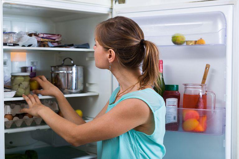Mujer mirando adentro de la heladera